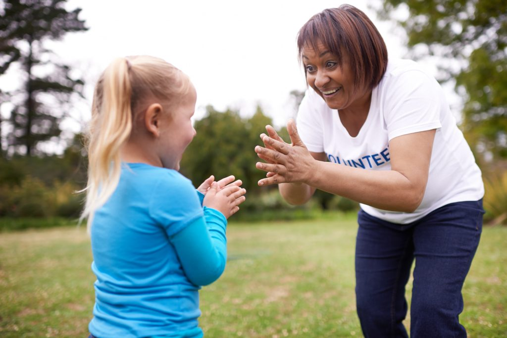 Volunteer clapping with young girl